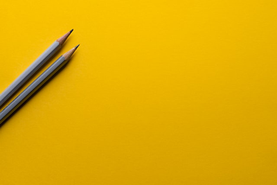 Image of two pencils on a yellow background
